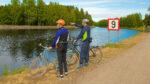 Kaksi pyöräilijää Saimaan kanavan varrella.