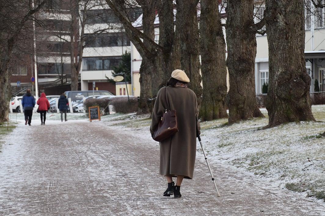 Vanhus kävelee kepin kanssa Lappeenrannan Kasinon edessä.