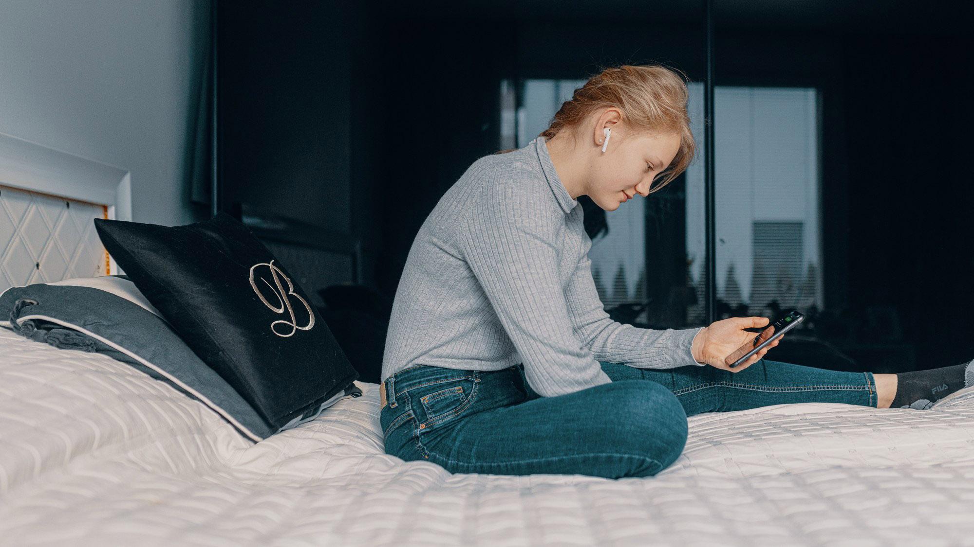 Tyttö istuu sängyllä ja katsoo kännykkää.