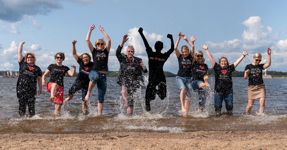 rekrytointi kuva ilmoitukseen: liiton ihmisiä pomppii Saimaan rannalla ilmaan.