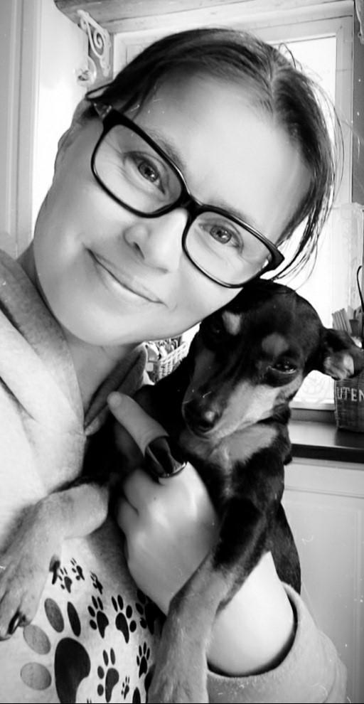 Sonja Tynkkynen pitelee sylissään koiraa.