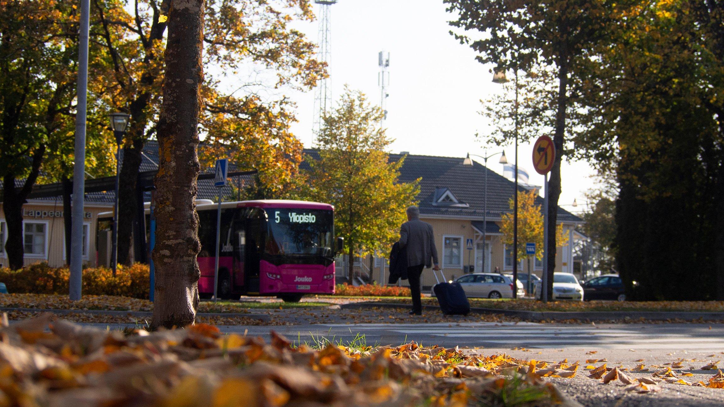 Syksyinen maisema Lappeenrannan matkakeskukselta. Etualalla on yliopistolle menossa oleva linja-auto sekä mies matkalaukun kanssa.