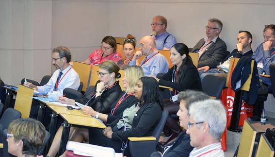 Ihmisiä istuu auditoriossa.